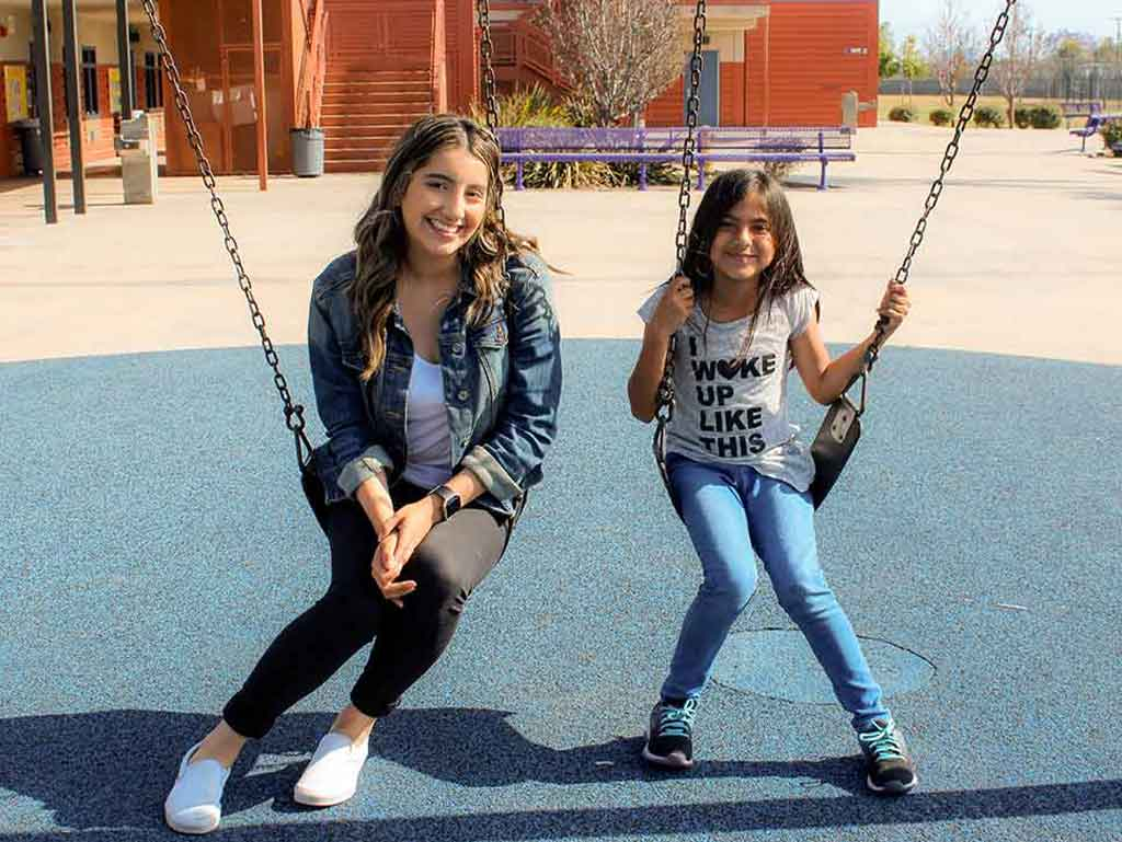 A high school mentor and her elementary school mentee swinging on the school playground
